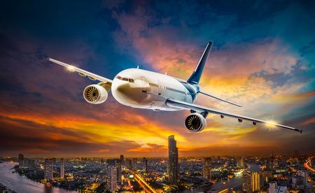 Vliegtuig voor vervoer vliegen over de nachtscène stad op de prachtige zonsondergang op de achtergrond