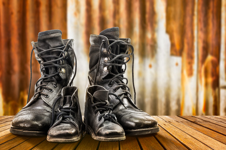 military boots: Combat boots for adult and kid on wooden floor and rusty galvanized iron wall in family concept Stock Photo