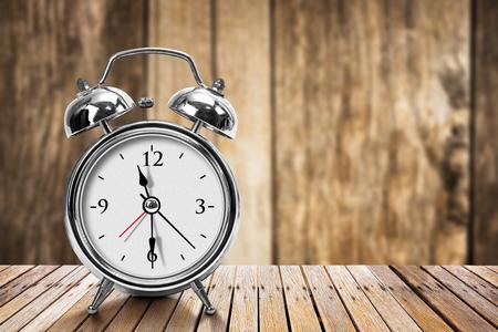 resonate: Modern silver metallic alarm clock on wooden table in vintage style Stock Photo