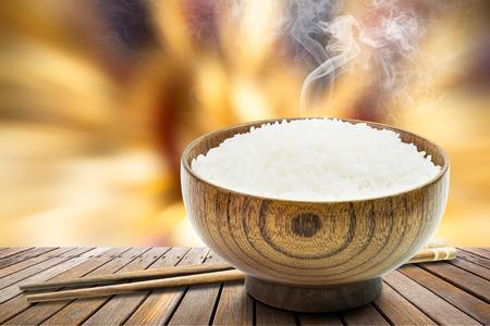 arroz: arroz cocido en un tazón y palillos de madera con humo en la tabla Foto de archivo