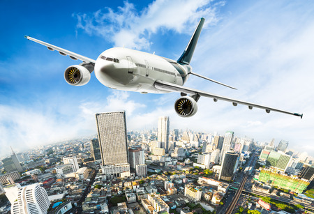 Airplane for transportation flying over the beautiful cityscape