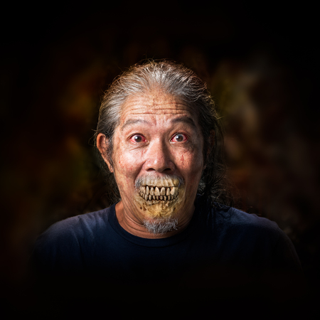 psychopath: Portrait of the old man vampire on dark background Stock Photo