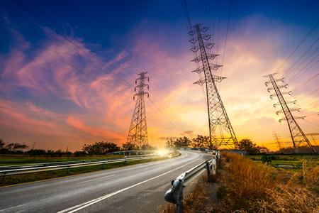 일출 배경에 높이 전압 전기 철 탑 시스템