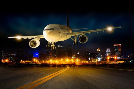Atterrissage de l'avion d'affaires à la piste de l'aéroport dans la scène nocturne Paysage urbain