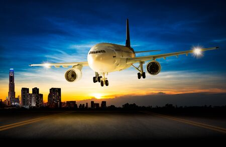 Landing business aeroplane to the airport runway in the night scene cityscape background