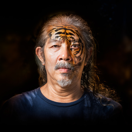 Old monster man transform the face to the siberian tiger