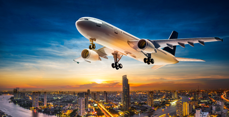 Business aeroplane take of over the cityscape on beautiful sunset background