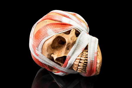 Human skull bind with blood stain bandage on dark background Stock Photo