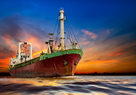 Industrial ocean ship on the sunset background