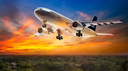 Airplane for transportation flying over the rural scene on beautiful sunset background