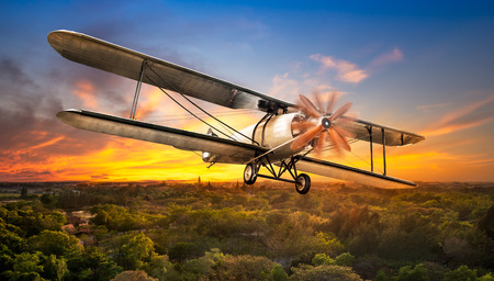 Ancient airplane flying over the rural scene on sunset background