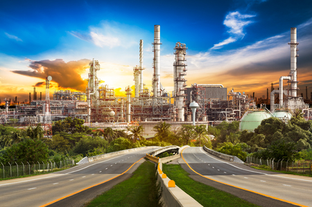 destilacion: Road to oil refinery industry in rural scene on sunset background Foto de archivo