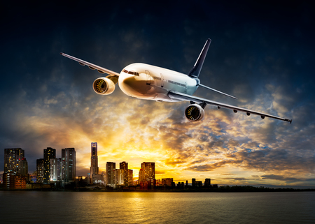 Airplane for transportation flying over the city at riverside and beautiful sunset background