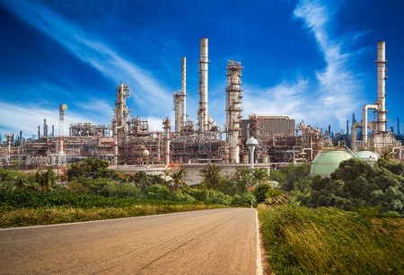 Road to the oil refinery on blue sky background