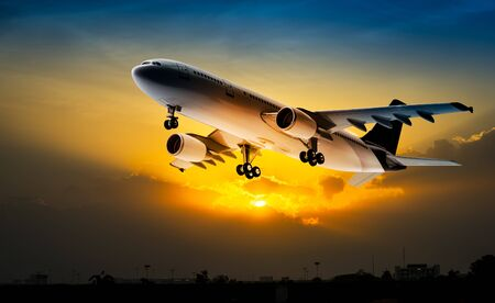 Airplane for transportation flying on the sunset sky