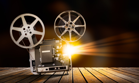 Vintage 8 mm movie projector on wooden table in the theater Stock Photo