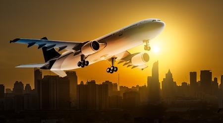 Flugzeug für den Transport, der über die Stadt auf schönen Sonnenunterganghintergrund fliegt