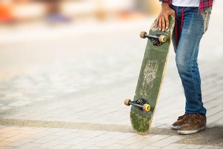 Skateboarder man hold on old skateboard at public park playground