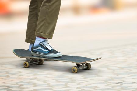 Skateboarder man keep on skateboard at public park playground