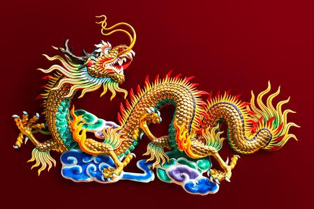Chinesische goldene Drachenstatue zur Dekoration im öffentlichen Tempel isoliert auf rotem Hintergrund mit Freistellungspfad
