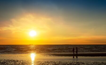 Couple walking at the beach in sunset time, romantic lovers concept