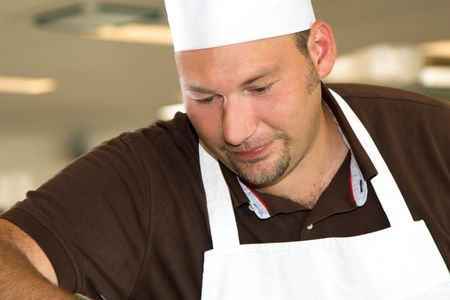Italian chef working in the restaurant kitchen concentrating on his work