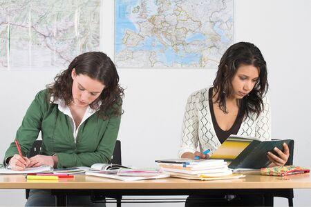 Twee meisjes op school buigen over hun boeken