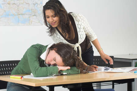 Teenage girls in a classroom; one of the girls has fallen asleep photo