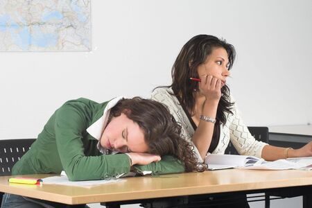 Two teenage girls in class; one has fallen asleep and the other is looking bored out of the window photo
