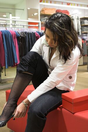 trying: Teenage girl in a store trying on new shoes Stock Photo