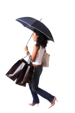 Beautiful brazilian girl carrying an umbrella and a lot of shopping bags, excited look on her face photo