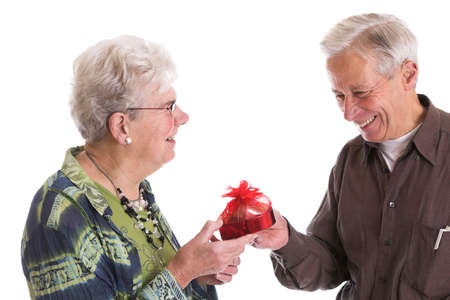 Senior couple celebrating valentines day together, with the man giving his wife a box of heart shaped chocolates photo