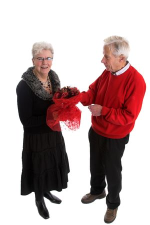 Pretty elderly lady getting a bunch of red flowers from her husband for valentine day photo