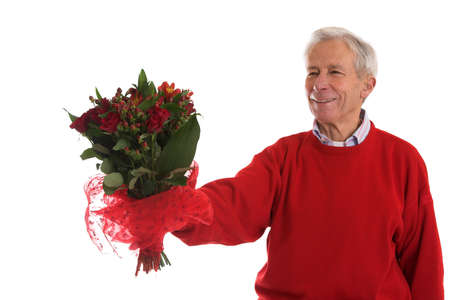 Senior man holding out a bouquet of flowers for his lover at valentine photo