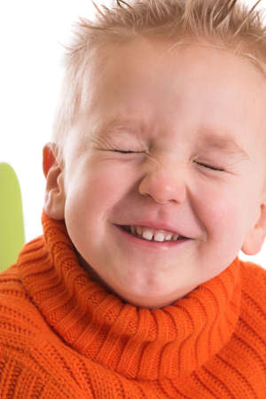 Two year old boy keeping his eyes firmly shut while laughing Stock Photo
