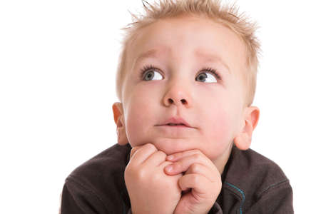 Cute two year old boy leaning on his hands with a contemplative look on his face