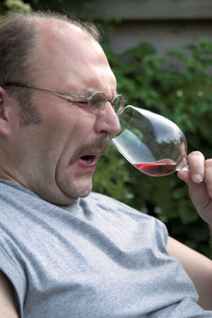 Man pulling up his nose in disgust while smelling a glass of wine Stock Photo - 851895
