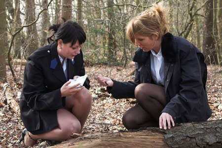 female cop: Two female police officers working on forensic research