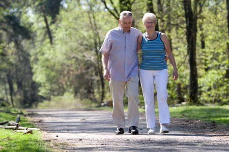 Lovely senior couple strolling through the park arm in arm photo