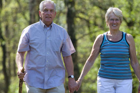 Elderly couple walking through the parc on a summer day Stock Photo