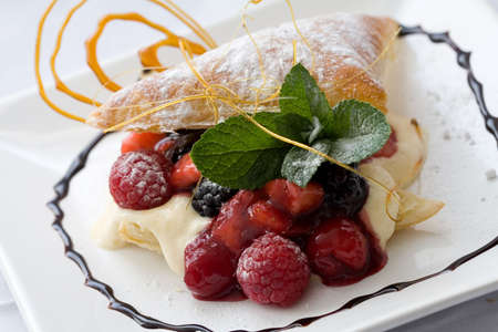Delicious pastry dessert filled with fruit on a decorated plate