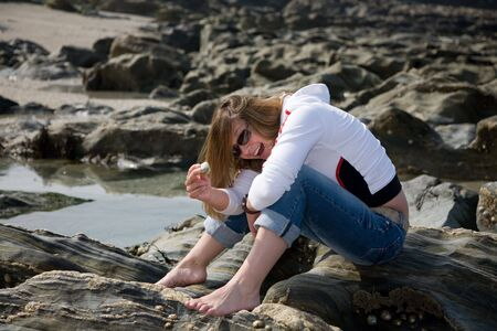 Pretty brunette sitting on the rocks by the side of the sea looking for clams and mussels photo