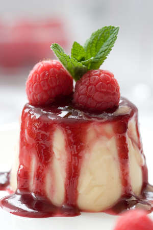 Small panna cotta covered with strawberry sauce and decorated with fresh raspberries and a mint leave photo