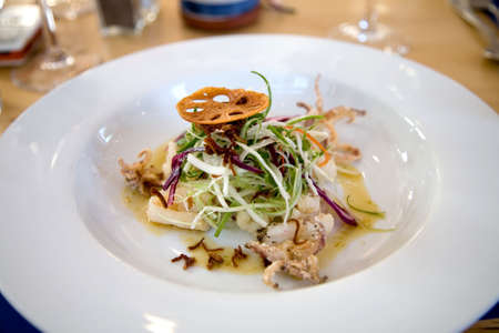 Salad of fried pieces of squid topped with salad and lemon dressing Stock Photo