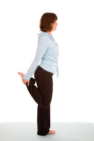 quadriceps: Pretty brunette standing on one leg doing a quadriceps stretch Stock Photo