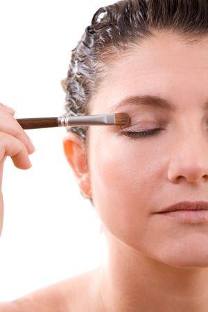 Beautiful brunette with a makeup brush applying eyeshadow photo