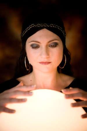 bola de cristal: Pretty gitana mujer con sus manos sobre una bola de cristal dice la futura  Foto de archivo