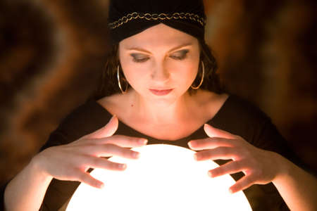 fortunetelling: Pretty gypsy woman with her hands above her crystal ball predicting the future Stock Photo