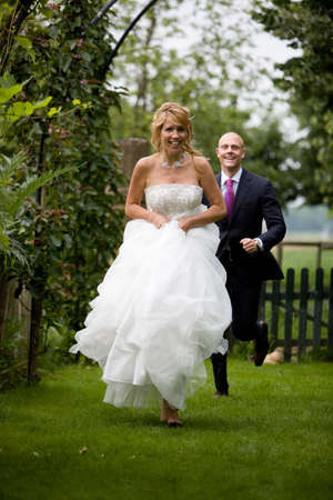 big smile: Beautiful bride running away from her new husband with a big smile on her face Stock Photo