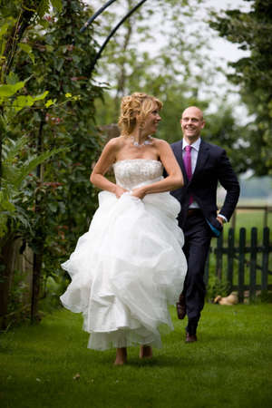Beautiful bride running away from her new husband on barefeet through the grass photo